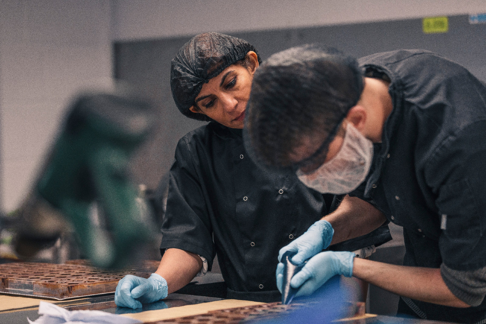 Mona Shah in protective gear and blue gloves looks across at young man in similar outfit who is bending over and piping chocolates in the factory.