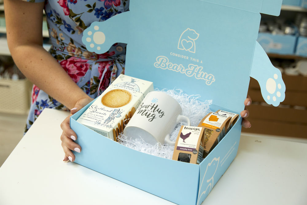 Image of pastel blue box filled with white tissue paper and tea, a mug and cookies