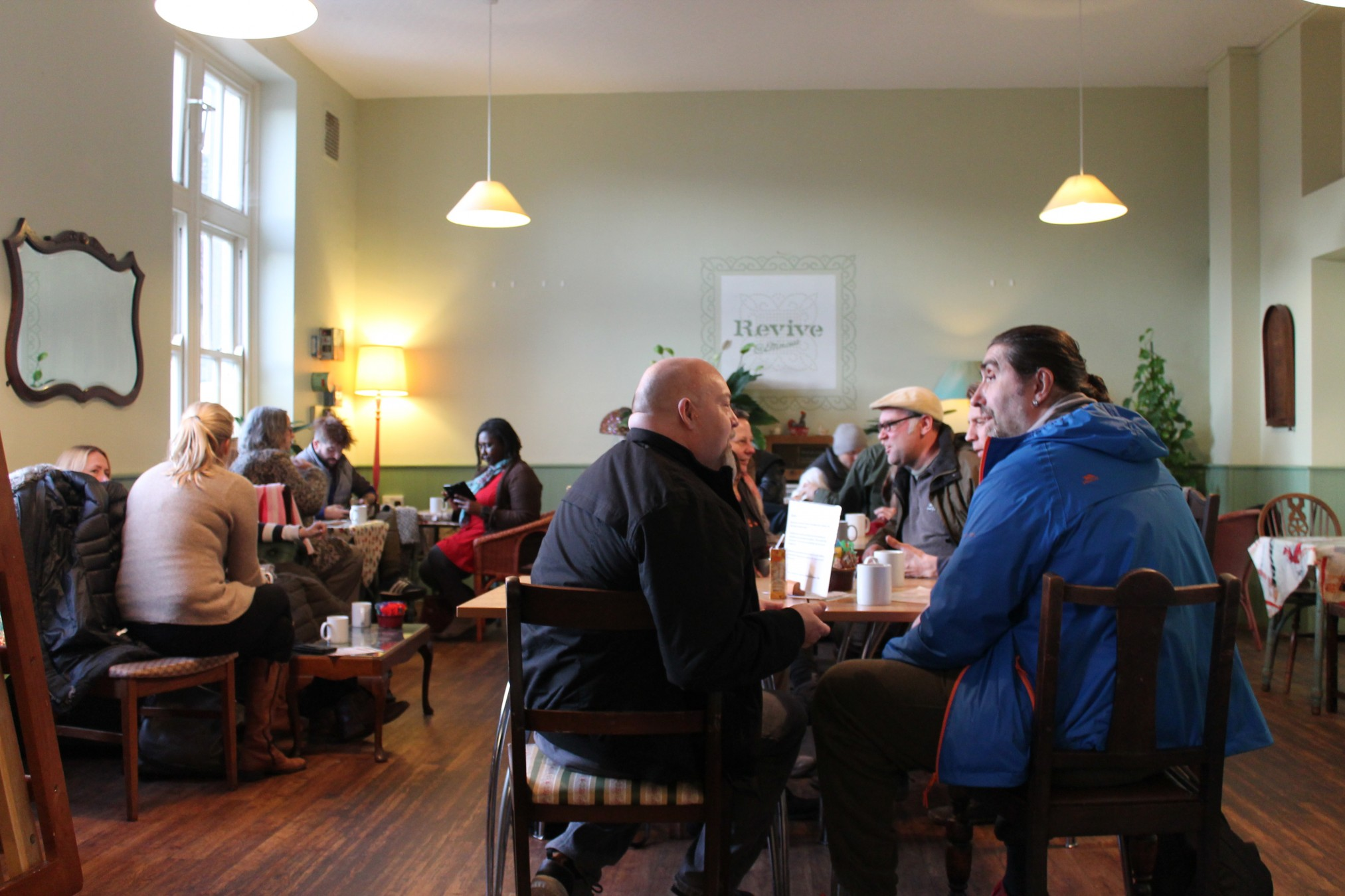 People from Brighton sitting at cafe style tables around a room with high ceilings