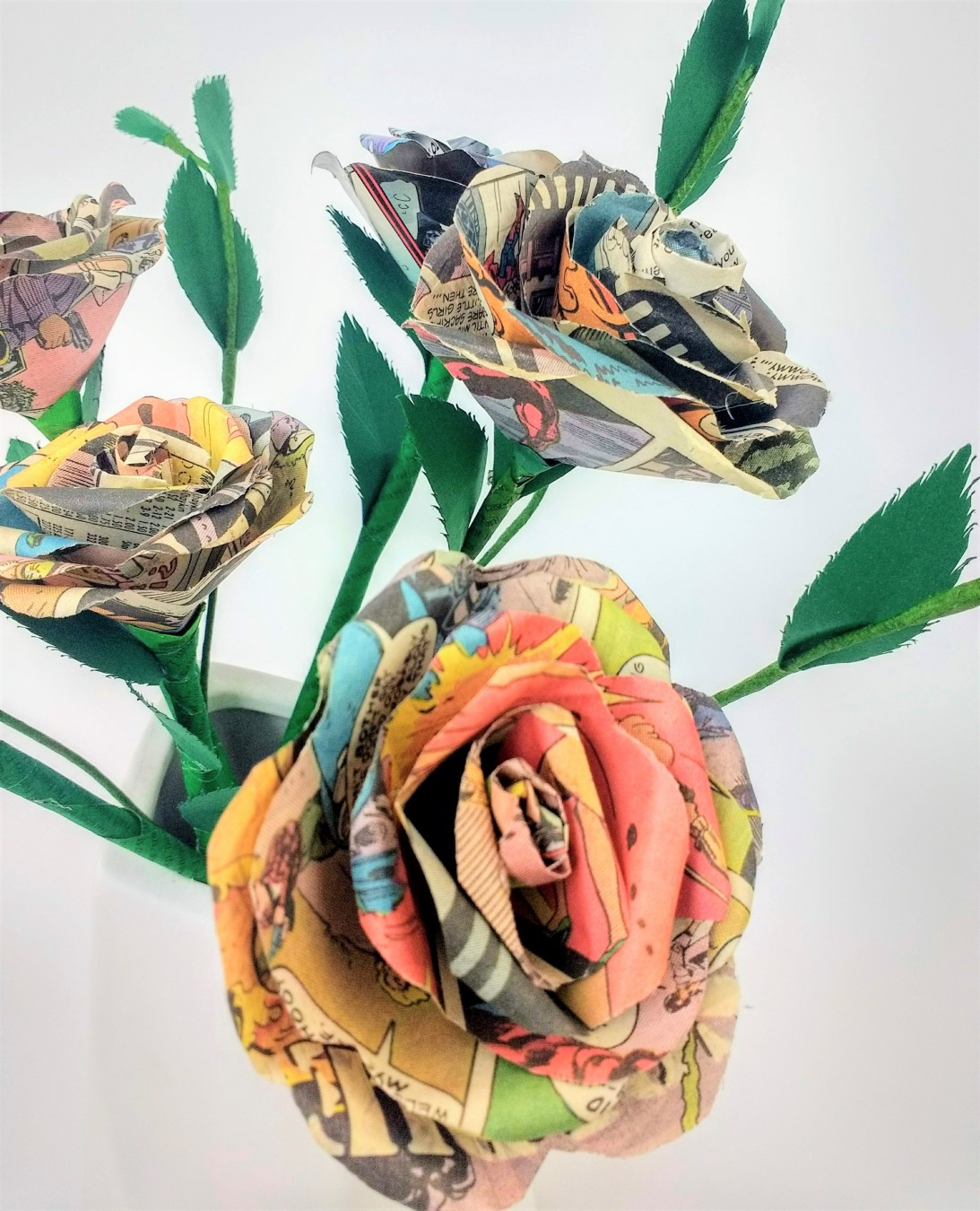 Close up of 3 paper roses with soft pink comic book print, and bright green stems.