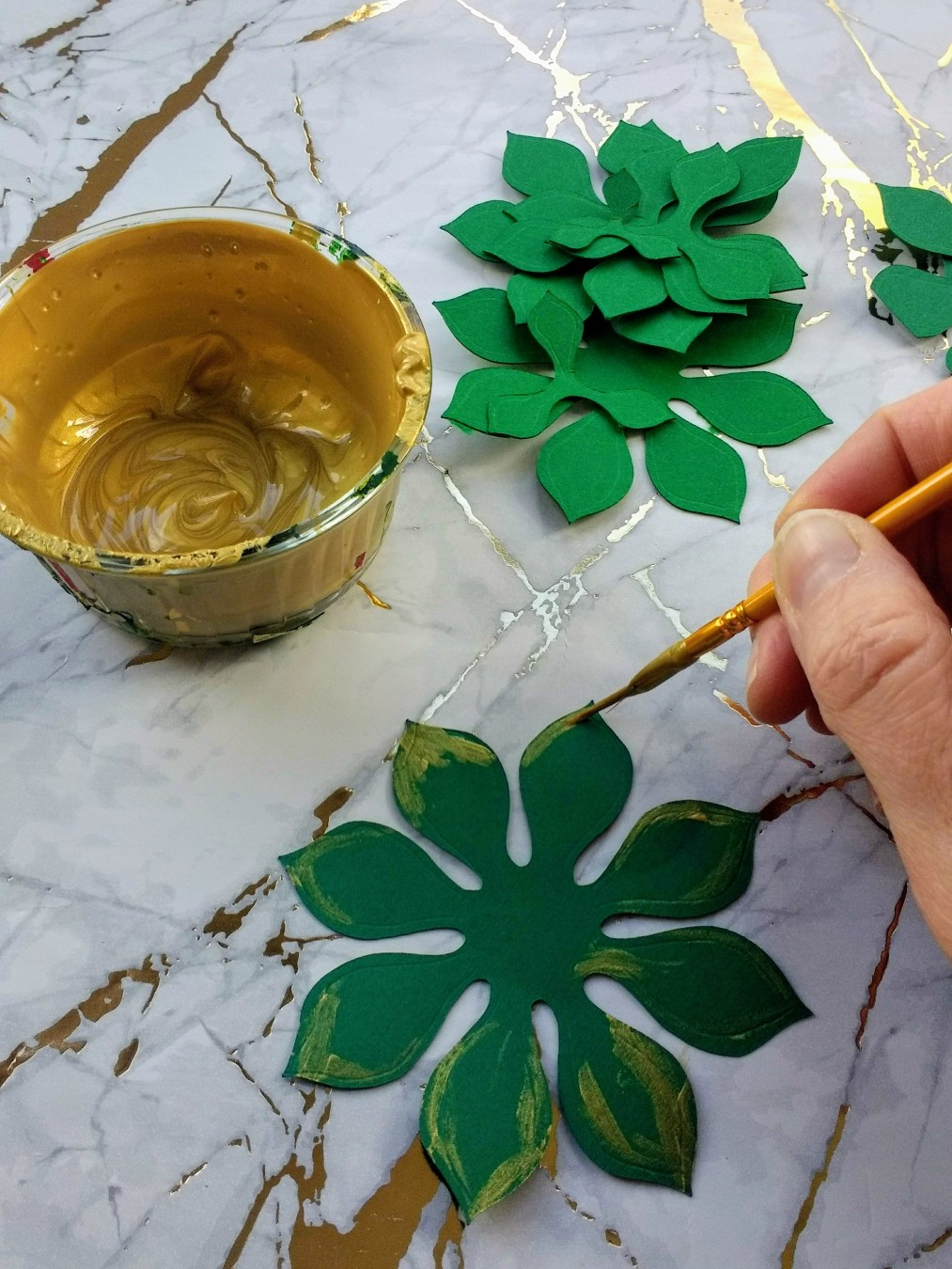 Image of a hand painting some green paper flowers with gold paint