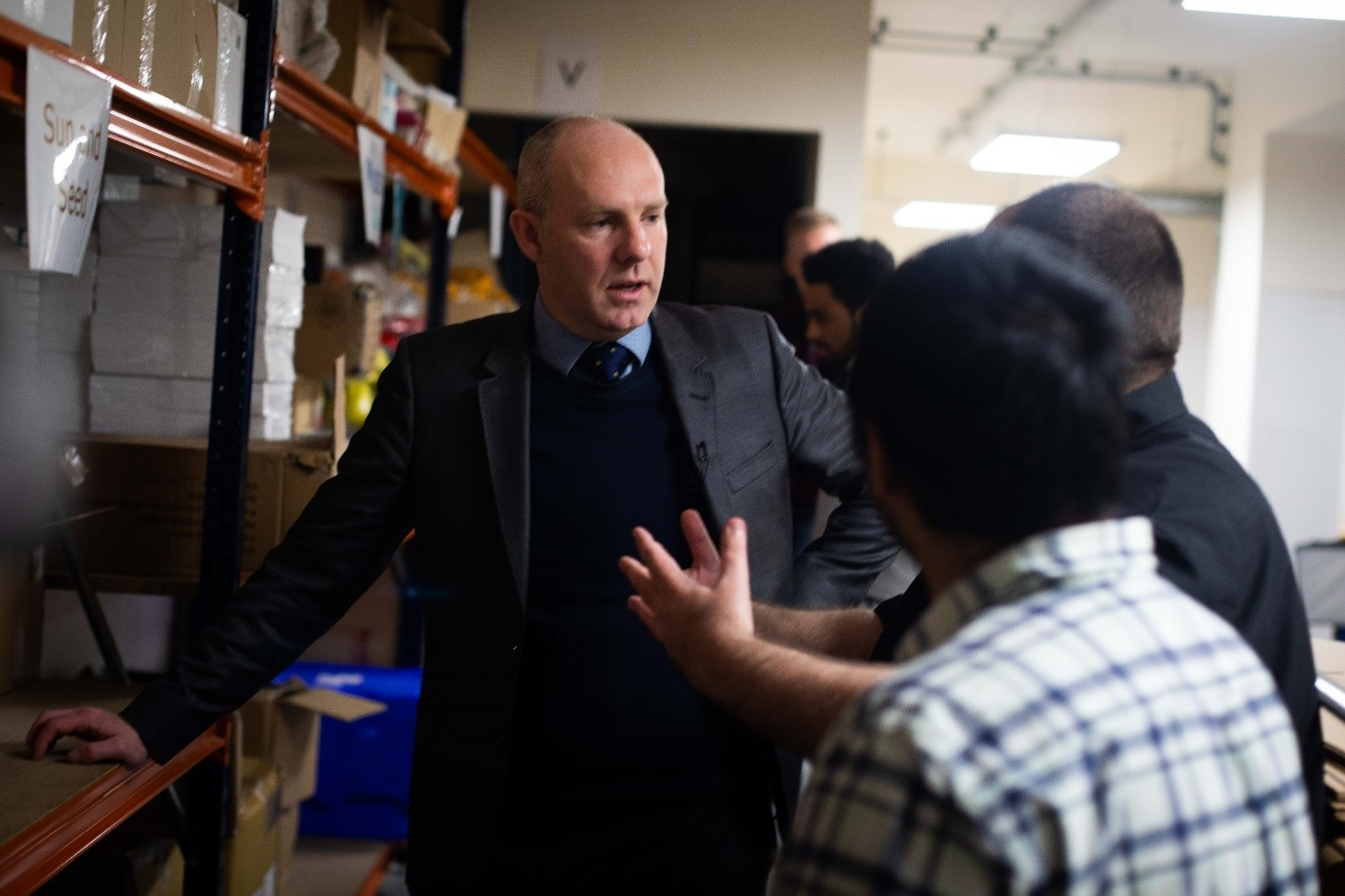 Government minister Justin Tomlinson in a warehouse, with one hand on hips and another on an orange shelf. He is speaking to 2 people with their backs to you.