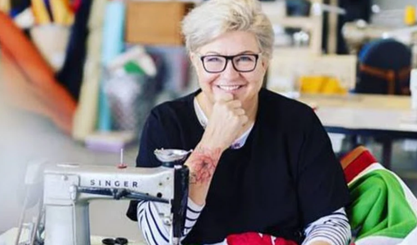 Image of Jo Ashburner Farr at a sewing machine working on a flag design, looking at the camera.