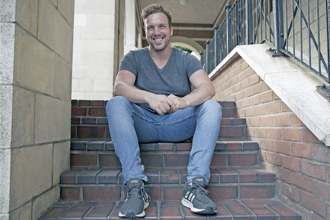 CareCalls founder Max Pownnall sitting on concrete stairs outdoors wearing jeans and a grey shirt. He is smiling directly at the camera.