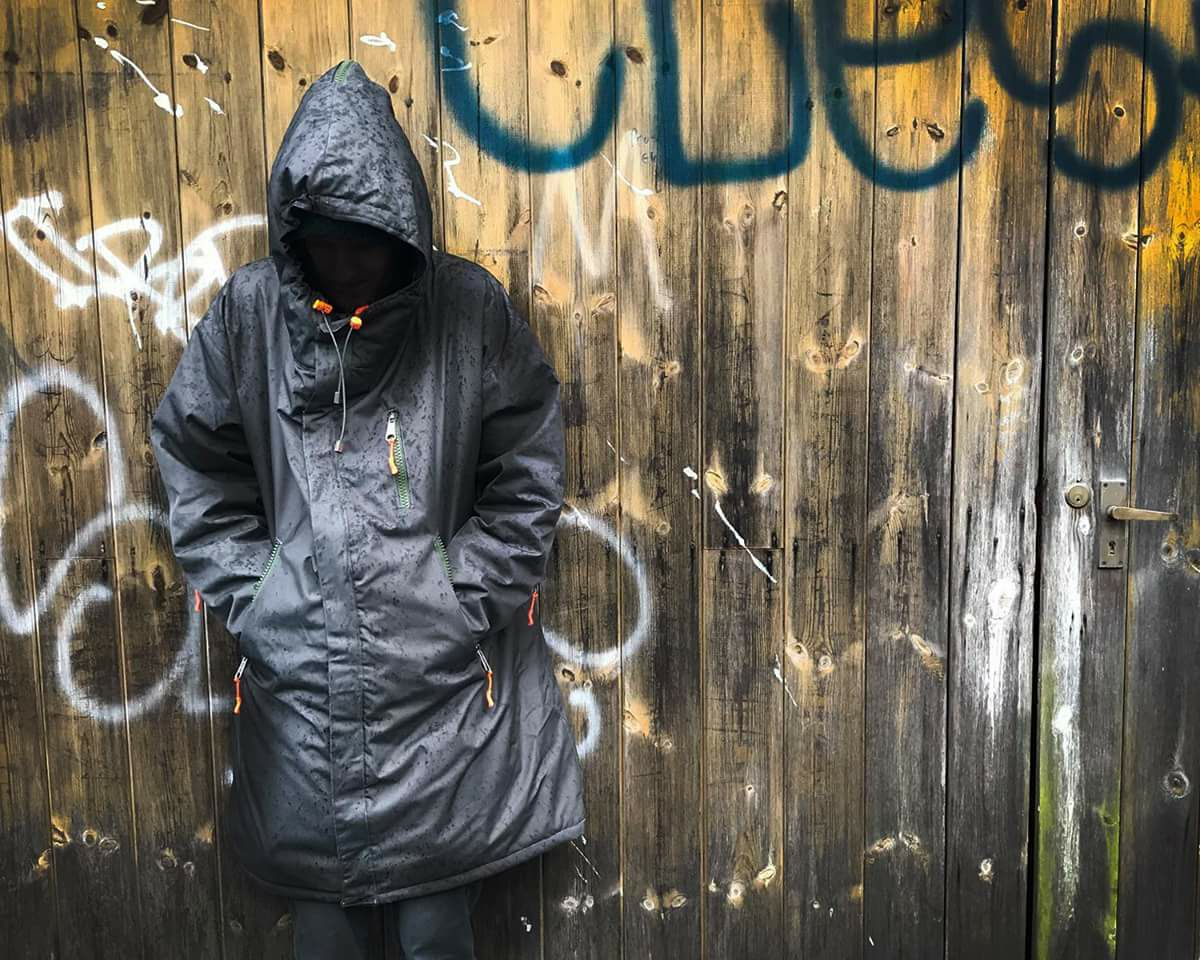 Image of man in front of a wall wearing the ROOF coat bag, with the hood up