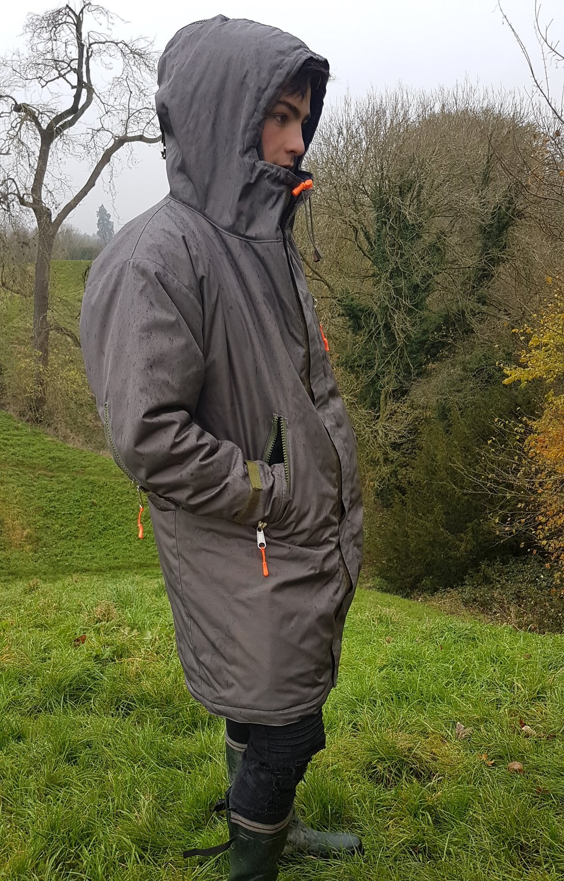 Image of man in the countryside wearing the ROOF coat bag, with the hood up