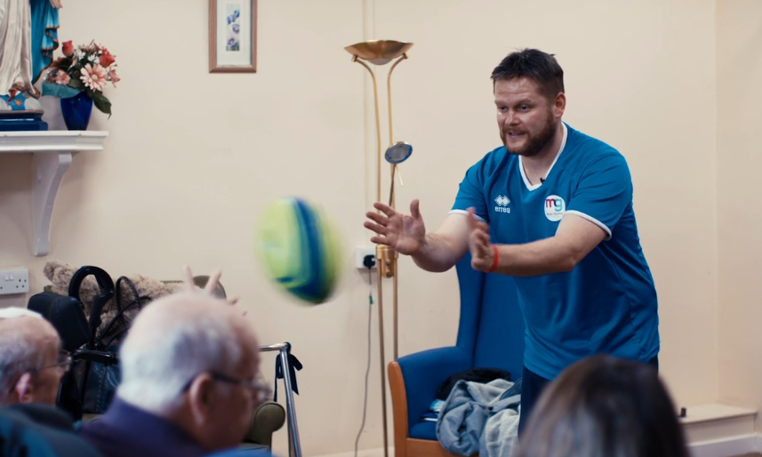 Image of man in a blue tshirt at a care home throwing a blurred rugby ball