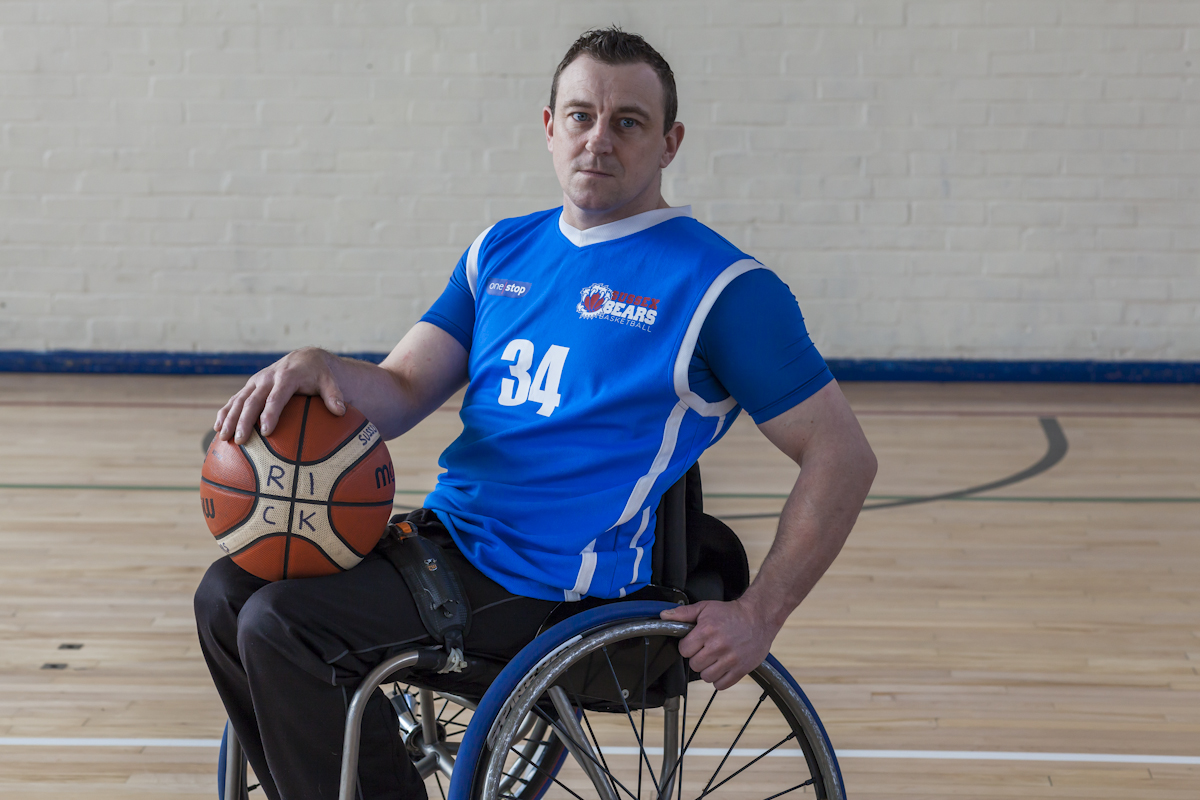 Photograph of Ricky Perrin, three quarters close of him sitting in a wheelchair slightly tilted back and holding a basketball.