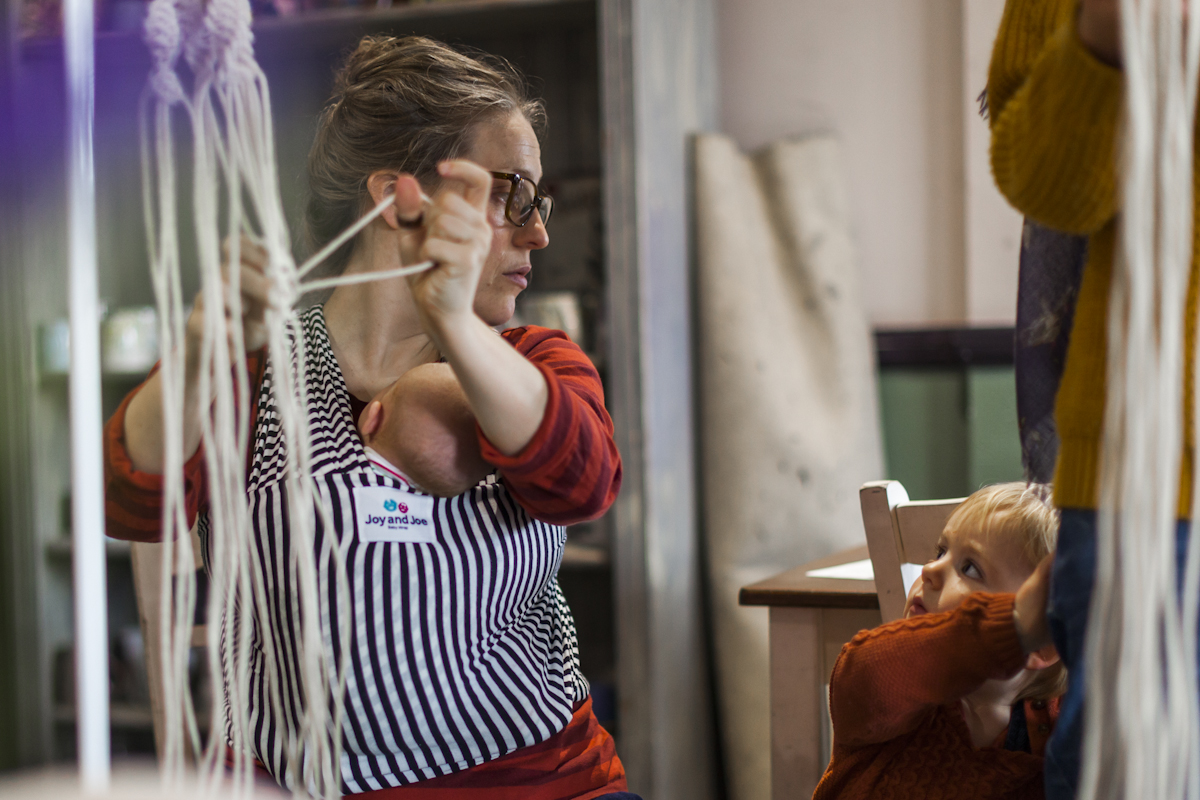 Woman with baby carrier working at weaving with small child to her right looking up.