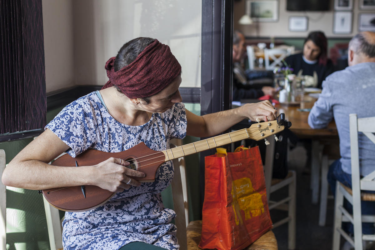 Image of woman tuning small guitar in the Bevy pub.