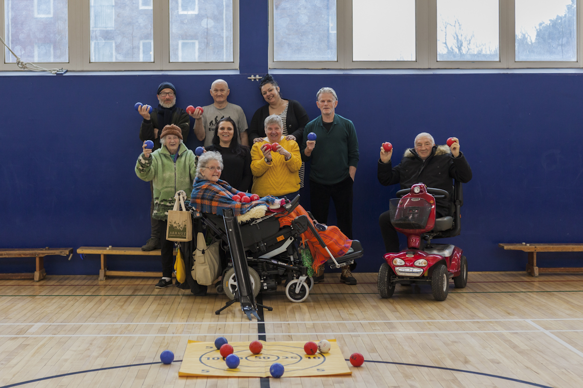Group of boccia players posing together against the blue wall of a gym with several small balls on the ground in front.