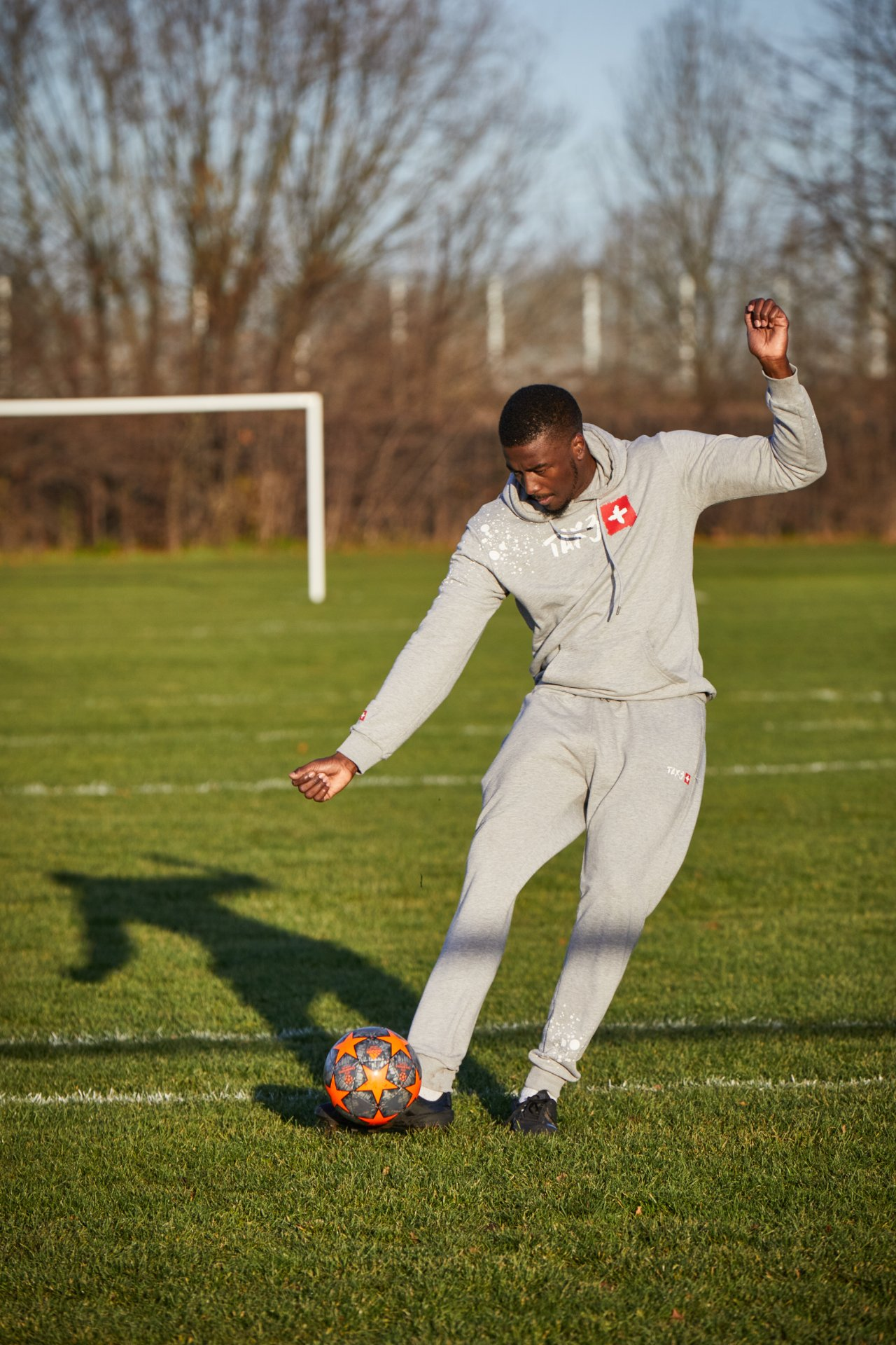 A Black man wearing a gray tracksuit kicking a football with his right foot