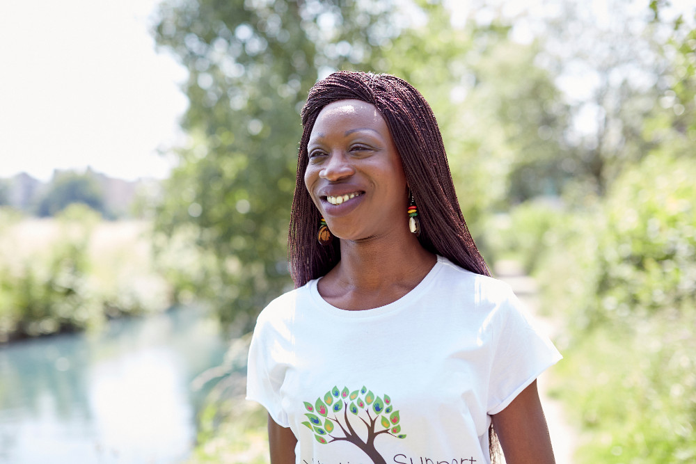 Fatou Gassama, the founder of Holistic Support, standing in front of trees in bright light.nd