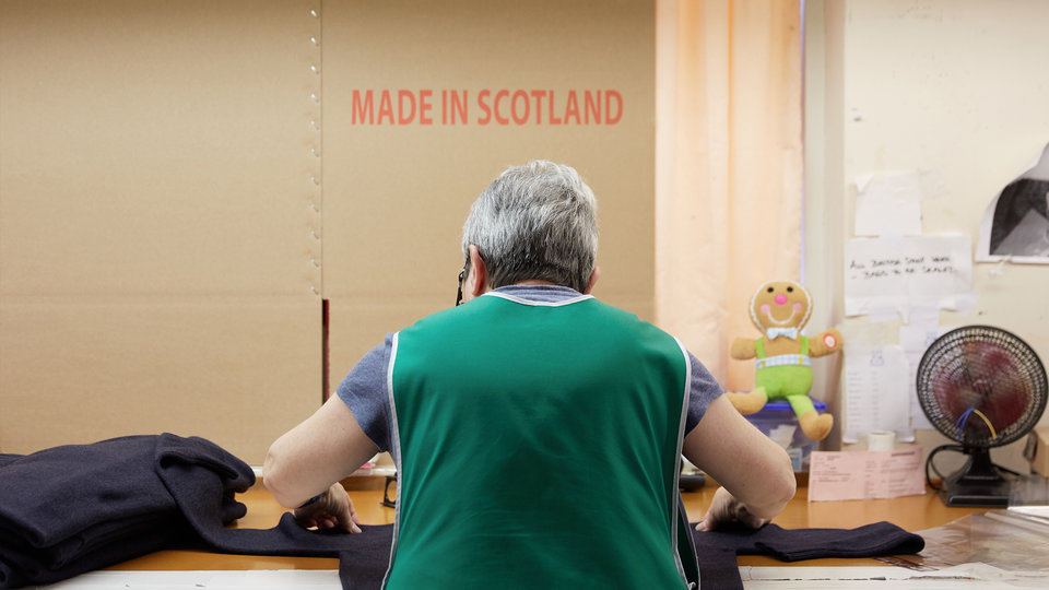 Woman working on a sewing machine with Made in Scotland written in red on the wall above her