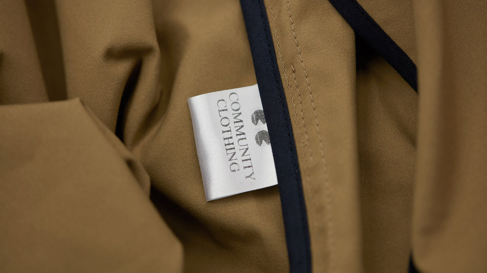 Brown clothing with a navy trim that has a tag which says Community Clothing